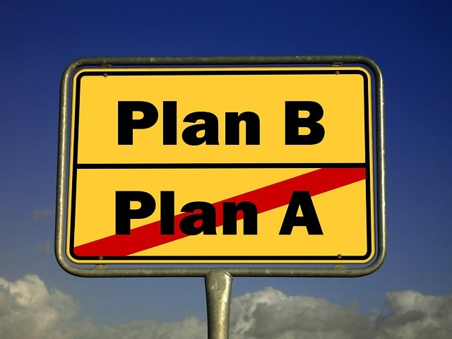 """Ortstafel, wo """"Plan A"""" durchgestrichen ist. Darüber ist """"Plan B"""" angebracht."""
